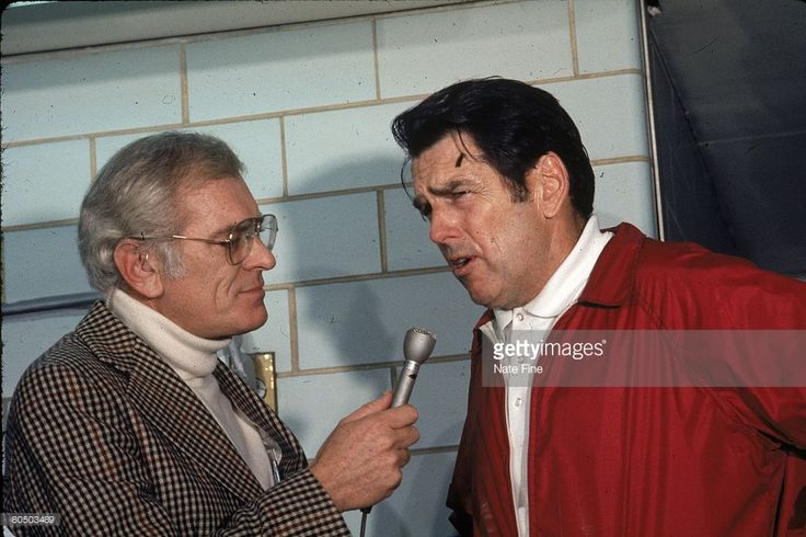 Head coach George Allen of the Washington Redskins talks with broadcaster Jack Whittaker of CBS in the locker room after the 1972 NFC Championship Game on December 31, 1972 in Washington, D.C. The Redskins defeated the Dallas Cowboys 26-3.