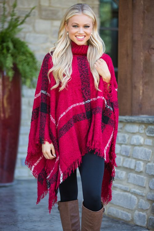 You're going to stay classy all season long in this gorgeous plaid poncho! Featuring a classic combination of red, white, and black plaid, it's a knockout look! It also features an adorable fringe detail, an asymmetrical hemline, soft knit material, and a comfy turtleneck for a fabulous fall look!