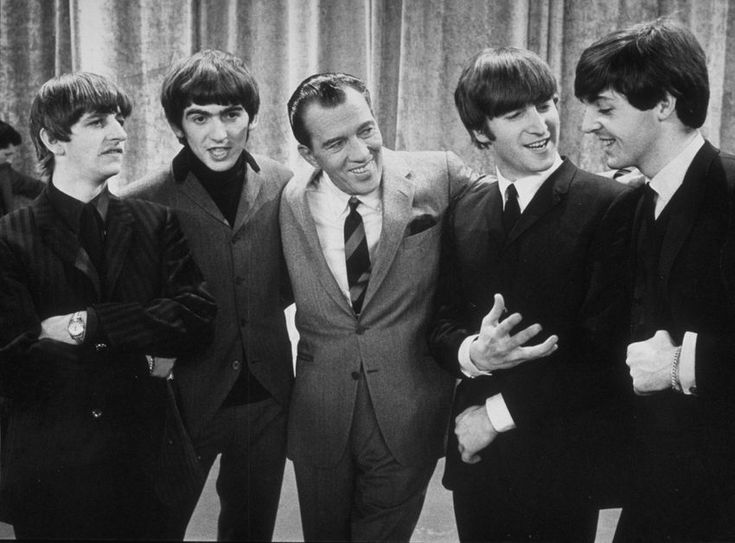 American television host Ed Sullivan smiles while standing with British rock group the Beatles on the set of his television variety series on Feb. 9, 1964.