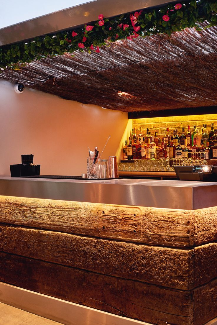 Outdoor bar area for restaurant. Chunky sleeper timber bar front with brushed stainless steel square edge top. Bar & Restaurant Design by Tibbatts Abel. Saint Paul's House. www.tibbattsabel.com