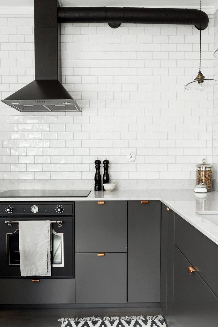 Fantastic Frank är en mäklarfirma som brinner för fantastiskt fotografi, fantastisk service och fantastiska affärer. // Scandinavian style kitchen with white subway tile, black hood, and dark grey cabinets with brass hardware.