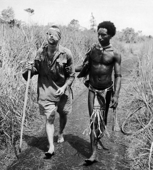 Papuan native helping a wounded Australian infantryman along road away from the Buna battlefront, 1942.