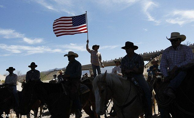 "Celebration: A supporter of the Bundy family flies the American flag after the Bureau of Land Management agreed to release the Bundy's cattle. But Bundy & Company had to go get the cattle. ""We have you surrounded...Give up the cattle...& so the Feds gave up the cattle!!!!!!!"""