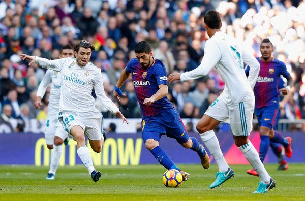 Luis Suarez of Barcelona is is challenged by Mateo Kovacic of Real Madrid during the La Liga match between Real Madrid and Barcelona at Estadio Santiago Bernabeu on December 23, 2017 in Madrid, Spain.