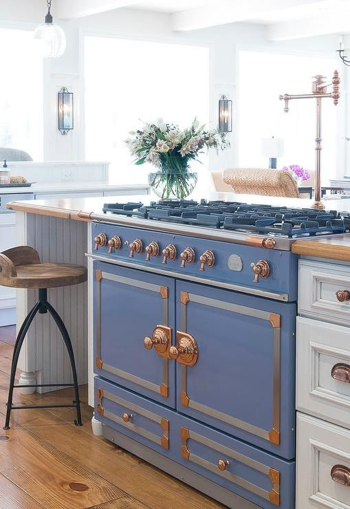 Beautiful kitchen features a white beadboard kitchen island topped with wood fitted with a French stove, La Cornue CornuFe Stove Provence Blue with Chrome, and a deck mount copper swing arm pot filler lined with Arteriors Henson Stools.