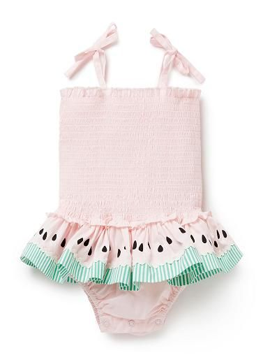 100% Cotton Romper. Woven romper with functional shoulder ties, and fully shirred body. Features 'watermelon' frill skirt with embroidered 'pips', rick-rack trim, and striped bind. Elasticated leg, with snaps on gussett. Neat fitting silhouette. Available in Shortcake.