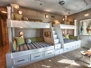 Custom Built Bunk Beds. Four bunk beds with ladder in the middle. Utilized the length and unique shape of the room by building a double twin-over-full bunk wall. #BunkRoom #BunkBed Cara McBroom, Licensed Interior Designer.