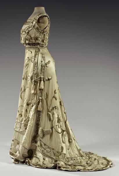 """""""WORTH (attribué à)  Thistles. Robe du soir, vers 1900. Tulle filet ivoire abondamment rebrodé en trapunto en relief de grands motifs, frises de trèfles et chardons en soie de tons or et ivoire."""""""