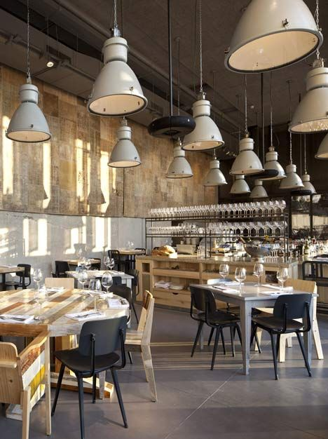 Industrial outdoor lamps hang over the tables of a restaurant in Tel Aviv by Israeli architects Baranowitz Kronenberg.