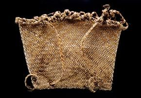 This is a kete pūkirikiri, or woven basket, made around 1904. Used to carry gravel to kūmara (sweet potato) beds, it is woven from haraheke (flax) using the raranga (plaiting) technique, whereby strips of leaf are laid diagonally. This is also an example of kete whakairo, or patterned basket weaving. The kete is yellow in colour with a twill pattern. It has plaited loops around the top for use with carry straps and also for lacing the kete closed, to keep objects secure. It measures 33.5 cm…