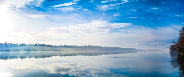 Morning Cloudscape - A clean white and blue scenery of clouds and their reflections on the surface of the Danube as rays of the early morning sun penetrate the vapor above the water.