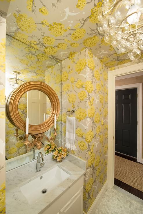 Exquisite yellow and gray powder room features carrera marble hexagon floor tiles leading to a white washstand fitted with a carrera marble countertop holding a sink with a polished nickel gooseneck faucet beneath a round gold leaf mirror with candle holders fixed to a frameless mirror framed by yellow and gray wallpaper matching a yellow and gray wallpapered ceiling.