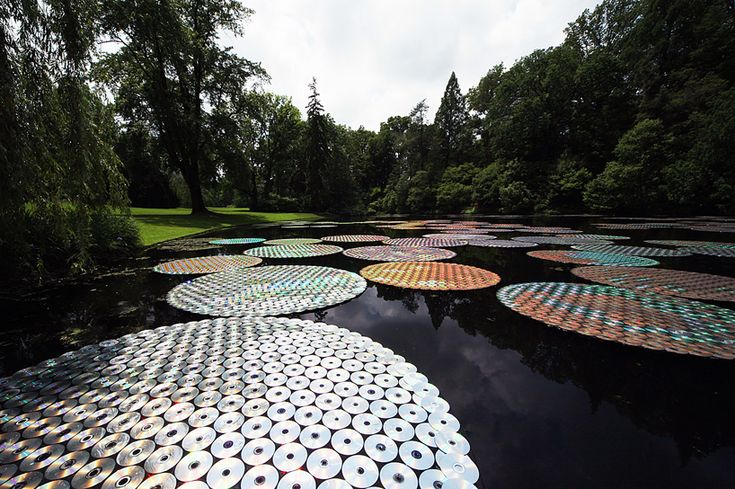 the artist's first large-scale solo show spans 23 acres and over ten installations, from a gently glowing forest treehouse and a rainfall chandelier to 200 floating lilypads composed of recycled CDs.