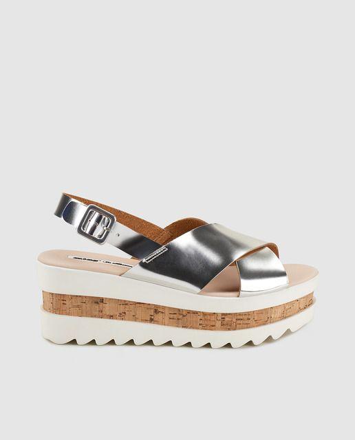Sandalias con plataforma en color plata con tiras cruzadas y cierre de hebilla.