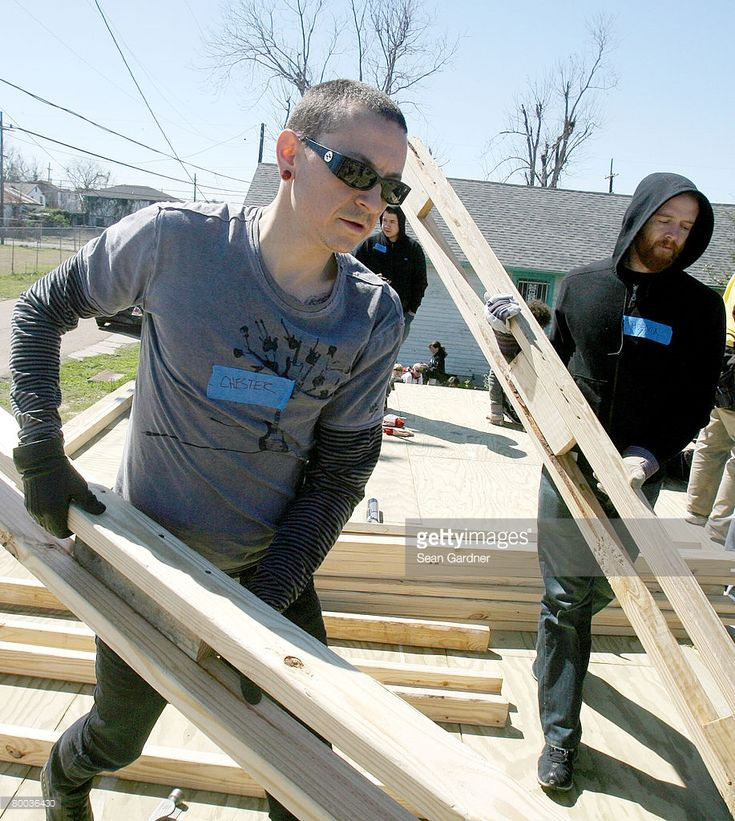 Chester Bennington (L) and Dave 'Phoenix' Farrell (R) of the band Linkin Park carry lumber to build frames as they work with Music for Relief and Habitat for Humanity while rebuilding homes affected by Hurricane Katrina on February 27, 2008 in New Orleans, Louisiana.