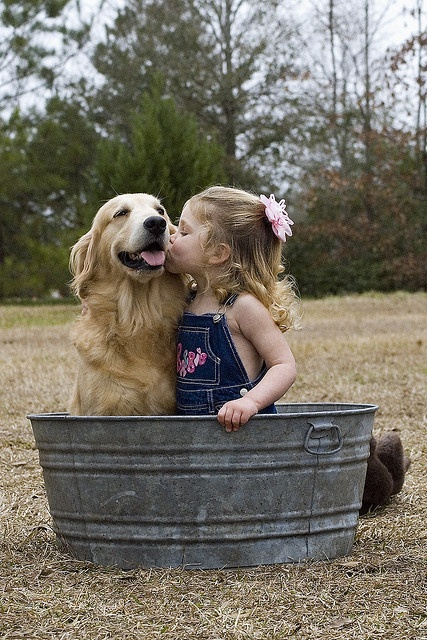 Little Girl In An Old Fashioned Bath Gives A Kiss To Her Golden