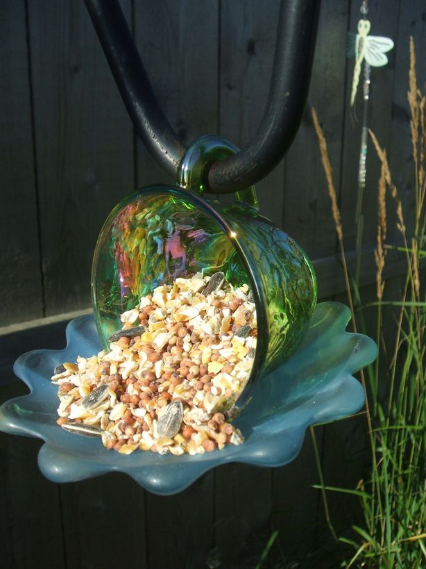 An upcycled teacup and saucer turned into a birdfeeder and hung on a sheperd's hook.