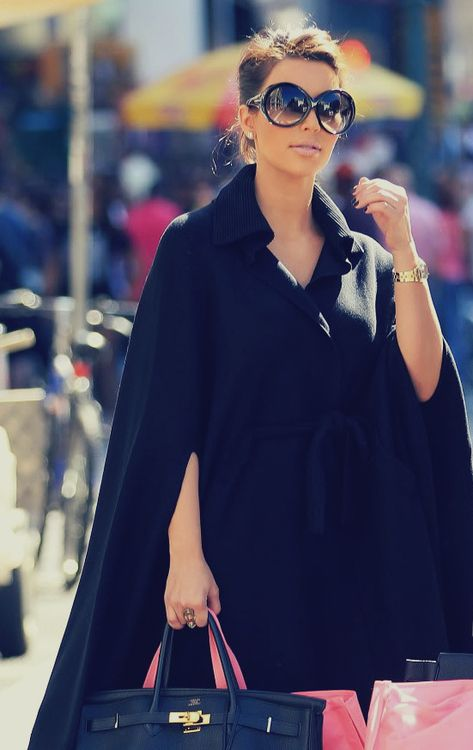 Kim Kardashian.... looks so cool! I want her sunglasses,bag and cape! #Kardashians...so stylish!