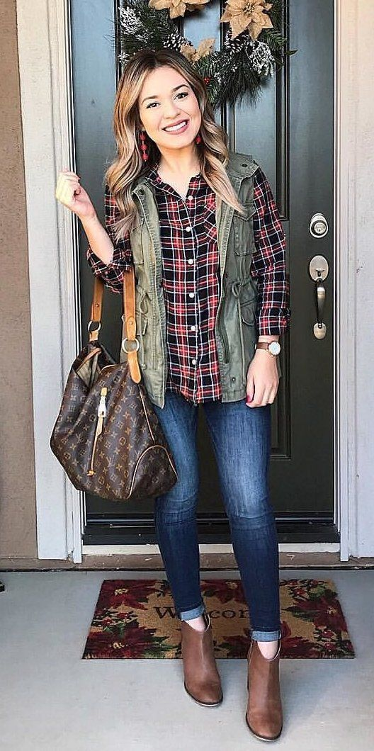 #winter #outfits green denim zip vest with red, black, and white plaid dress shirt, blue denim jeans, and brown leather booties outfit #jeansoutfit