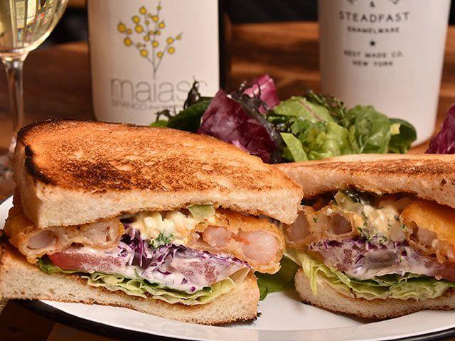 《 恵比寿 》「シュリンプ PO' BOY」(¥1,340)  『DAY&NIGHT』オーナー守口氏のおすすめは「シュリンプ PO' BOY」。アメリカ・ニューオリンズ州の名物料理をサンドイッチにアレンジしたという一品で、カリッと揚げたてのエビと、紫キャベツなどがタルタルソースと合わさって、噛む度にさまざまな食感が楽しめる。   自家製ベーコンを使用した「B.L.T」(¥1,340)や、オーブンで焼き上げたチキンとモッツァレラチーズを挟んだ「グリルドチキン」(¥1,290)なども人気だそう。定番メニューの他にも、旬の味を取り入れた月替わりサンドイッチも登場するので、いつ訪れても新しい味に出会えるだろう。