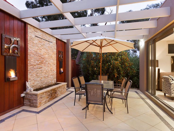 Walled outdoor living design with pergola & decorative lighting using tiles - Outdoor Living Photo 257044