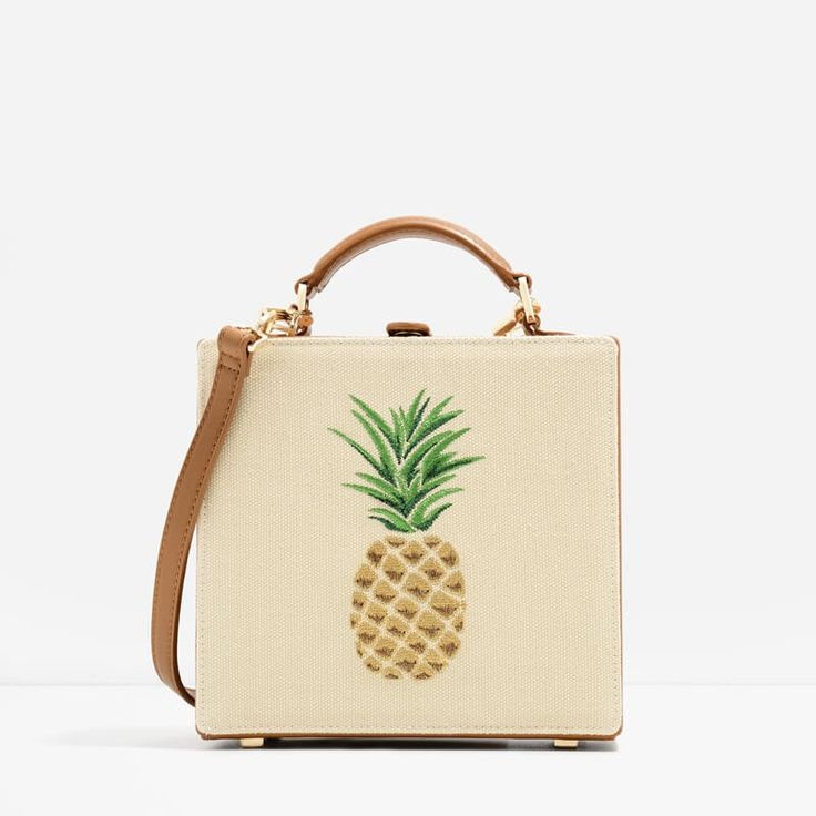 Mid-sized top handle boxy bag with a pineapple printed design in beige. Comes with an additional shoulder strap and fastens with a snap button closure.