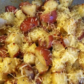 Red potatoes cubed with skin left on, drizzle with extra virgin olive oil, coat with a package of zesty Italian dressing mix and stir to coat, add minced onion for flavor, salt and pepper to taste. Cook 400 degree oven for 45 minutes or until tender. Top with grated Parmesan cheese.