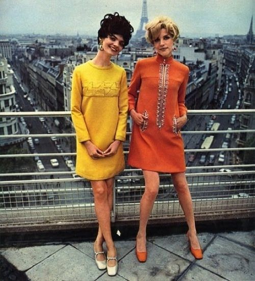 1960s models in bold, short, orange and yellow mod A-Line dresses with the Eiffel Tower in the background