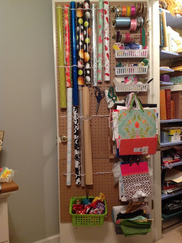 Wrapping Station On The Back Of A Door. Wrapping Paper Rolls Are Held Up By  Elastic Run Through Pegboard Holes, With U Hooks Under The Slippery Ones.