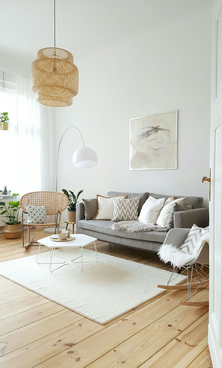 Bright and modern living room with a grey couch, a white rug and a light wooden floor. We love the Eames rocking chair, the woven pendant light and the curved floor lamp. #LampIdeas