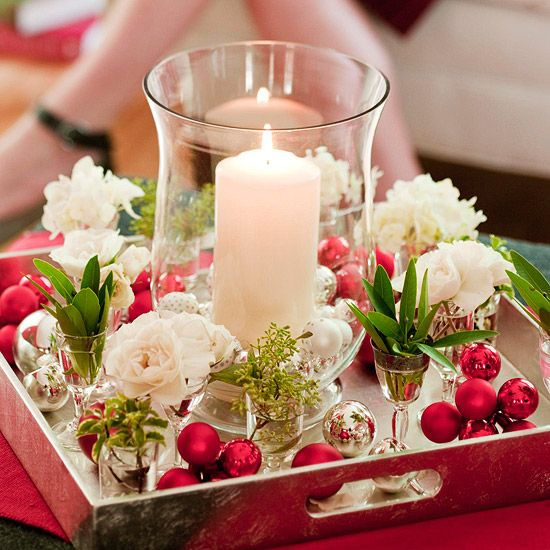 A pillar candle surrounded by smaller glasses  creates an elegant display. The candle inside the clear glass hurricane stands tall amidst small vessels filled with water and a single flower or sprig of foliage. Red metallic florist's picks and loose silver ornaments add color and sparkle.