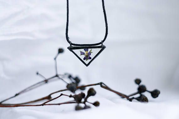 Triangle herbarium glass pendant with pansy flower inside.