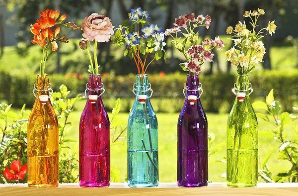 Arranjo de flores em garrafas coloridas