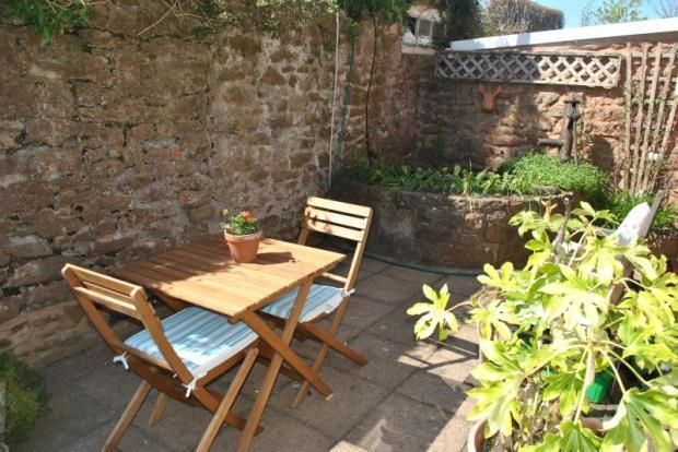 Ancient red sandstone wall & water trough makes protective spot in sunny Somerset garden