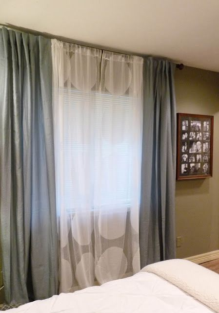 Make flat sheet curtains of cut colored queen size sheets on either side and a cheap white one in the middle to cover the unfinished window-holes.  Use spray painted electrical conduit for the curtain rod.  Should cost less than $15.