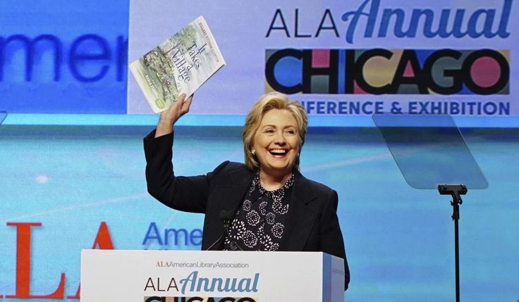 Hillary Clinton holds up an illustrated children's version of her book, 'It Takes a Village', as she speaks at the American Library Association (ALA) Annual Conference and Exhibition, Tuesday, June 27, 2017, in Chicago. (AP Photo/Teresa Crawford)