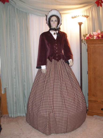 "SomeWear In Time - Original Designs  Part 1 - Burgundy Velveteen Outfit  Lined, Boned Burgundy Velveteen Jacket with vest front, short peplum v-neck and bell sleeves. Metal buttons adorn a false hook-and-eye front.  Woven homespun cotton cartridge pleated skirt of burgundy and oatmeal plaid.  White batiste tucker with buttons and black jet brooch - matching batiste undersleeves.  Matching Godey Bonnet has white silk ruched lining, black taffeta ""curtain"", and black grosgrain tie.  $650…"