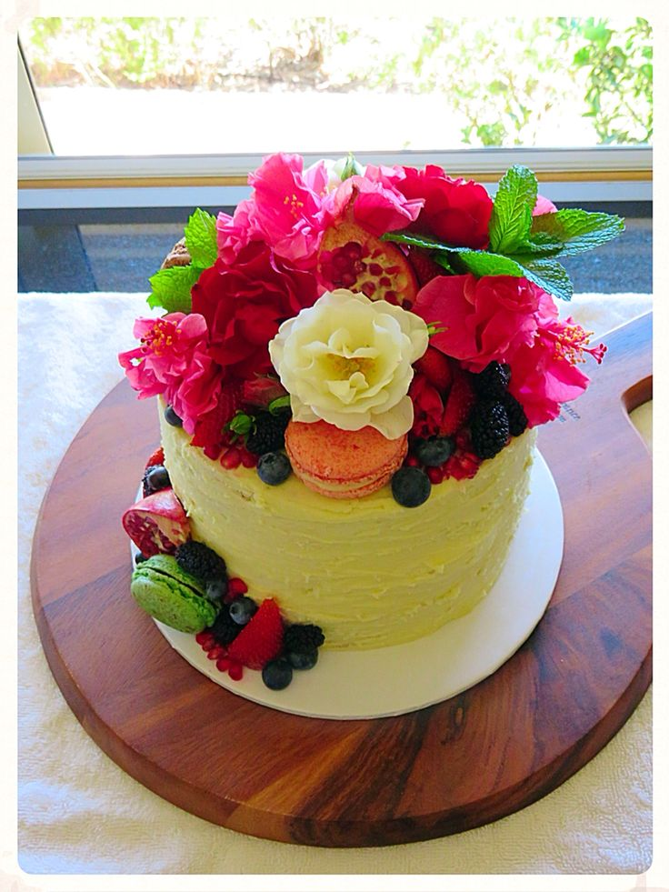 Buttercream cake with fresh flowers berries and macaroons