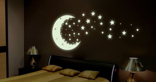 Glowing moon sliver and stars on the bedroom wall against a dark color of paint