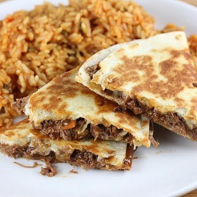 Mexican Shredded Beef Recipe - 1½lbs boneless beef chuck roast 1medium onion (sliced) 1cup beef broth 1(1¼ ounce) package taco seasoning mix 1(16 ounce) jar taco sauce 1(7 ounce) diced green chilies