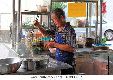 PENANG, MALAYSIA - APRIL 2012 : A man making noodles at noodle stall on Lorong Kampung Malabar street in Penang, Malaysia on April 18, 2012. Noodle soup is one of the most popular foods in Penang.   - stock photo