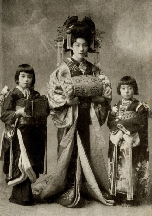 Satogiku-dayuu 1910s. It was customary for a tayuu (Japanese courtesan) to have two kamuro (child attendants) of about the same age and size, with names that matched in concept and sound, taking their cue from the name of their ane-jōro (elder sister courtesan). Text and image via Blue Ruin 1 on Flickr