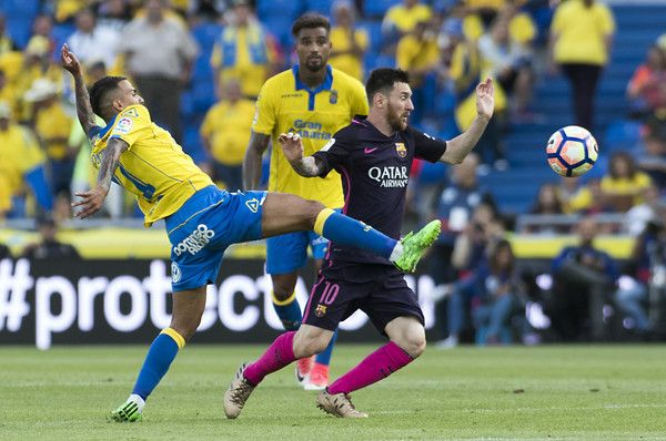 Barcelona's Argentinian forward Lionel Messi (R) vies with Las Palmas' midfielder Momo (L) during the Spanish league football match UD Las Palmas vs FC Barcelona at the Gran Canaria stadium in Las Palmas de Gran Canaria on May 14, 2017. / AFP PHOTO / JAIME REINA