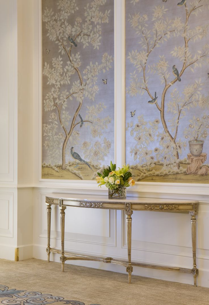 An elongated demilune gilded table is balanced by the soft sheen of shimmering blue panels, light airy and gorgeous.