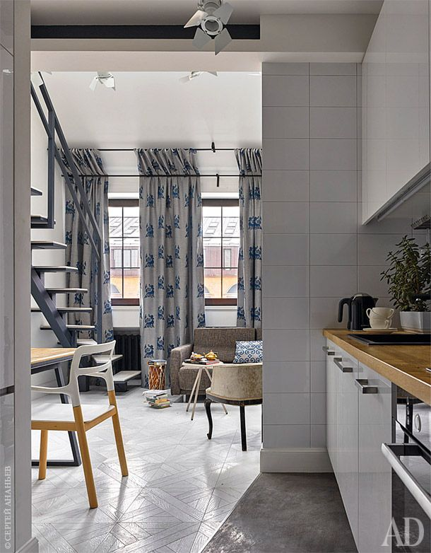 Бетонные полы прихожей и кухонной зоны контрастируют с белым модульным паркетом. Прием повторяется в ступеньках лестницы.