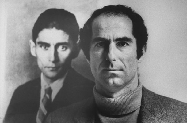 Pulitzer Prize- and National Book Award-winning novelist Philip Roth posing next to a photo of author Franz Kafka, whom he resembles in appearance & whom he owes much in the way of inspiration as a writer. (Photo by Bob Peterson//Time Life Pictures/Getty Images)
