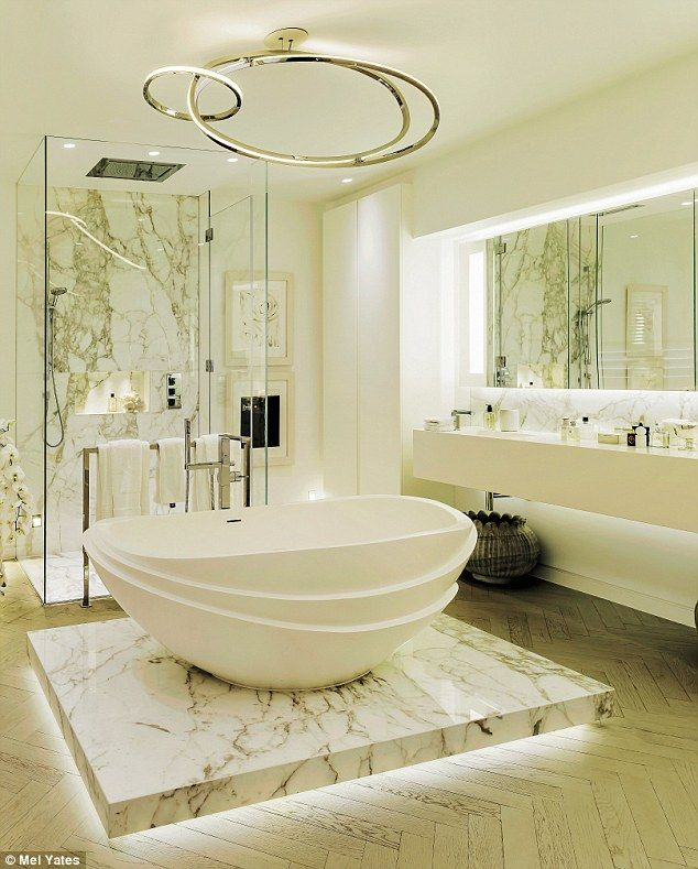 'The master bathroom is probably my favourite,' says Kelly. 'The bath I designed, made from reclaimed marble, is part of my collection for Apaiser [apaiser.co.uk] and inspired by lotus flowers.' The bathtub is set in the centre of the wooden floor on a Calacatta marble plinth, lit from beneath, to create a floating effect. The ceiling light sculpture is by Niamh Barry (niamhbarry.com)