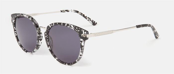Gafas de sol para mujer, con frente de pasta con estampado negro y transparente y puente y varillas de metal en color plata. La lente es gris. Entra en multiopticas.com y pruébatelas.