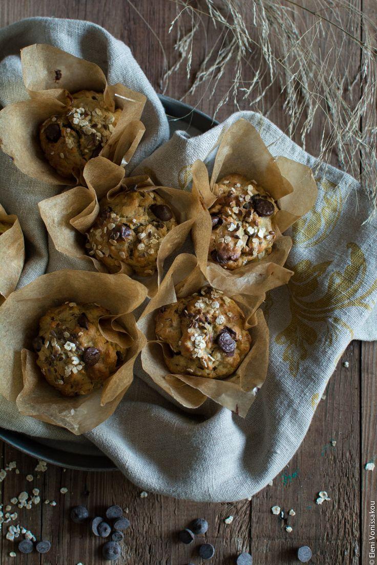 Μάφινς Μπανάνας με Βρώμη, Μέλι, Ταχίνι και Σταγόνες Σοκολάτας www.thefoodiecorner.gr Περιγραφή φωτογραφίας: Έτοιμα ψημένα μάφινς μπανάνας μέσα σε θήκες λαδόκολλας, τοποθετημένα σε ένα στρογυλλό ταψάκι στρωμένο με λινή πετσέτα κουζίνας. Γύρω από τα μάφινς, πάνω στην ξύλινη επιφάνεια, λίγα διακοσμητικά κλαδάκια από ξερά χορτάρια, λίγες σταγόνες σοκολάτας και νιφάδες βρώμης.