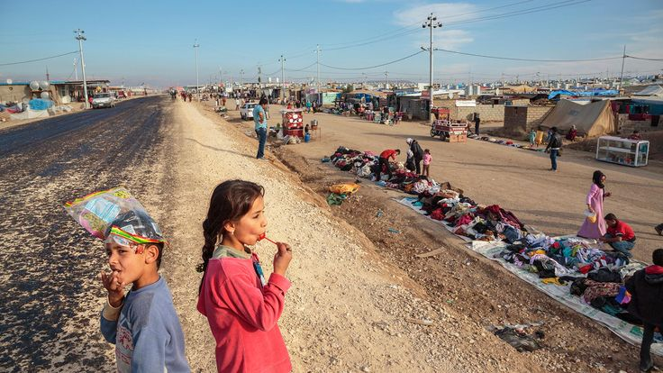 A young girl enjoys a lollipop while watching shoppers in the Domiz Camp for Syrian Refugees in Dohuk, Iraq, 2013 - by Ed Kashi (1957), USA
